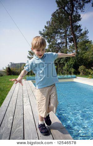 Portrait of a little boy walking beside a pool