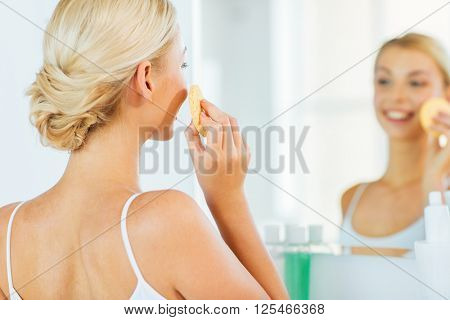 beauty, skin care and people concept - close up of smiling young woman washing her face with facial cleansing sponge at home bathroom