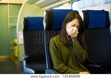 Woman sneeze inside train compartment
