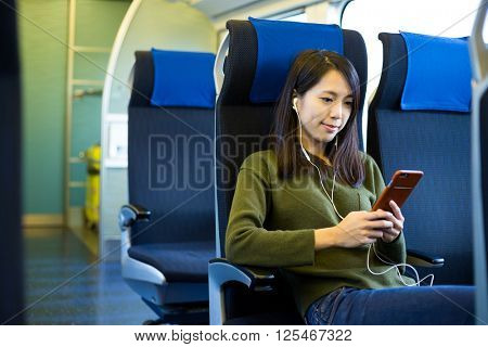 Woman listen to music and sitting inside train compartment