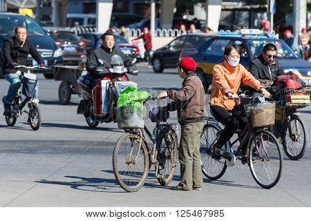 Beijing China - October 15 2013: Bicyclists and bikers on the street in Beijing China. Bicycles are a common form of transportation in the country.