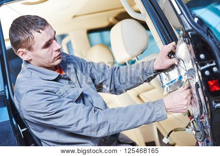 auto mechanic placing the damping mats on car door