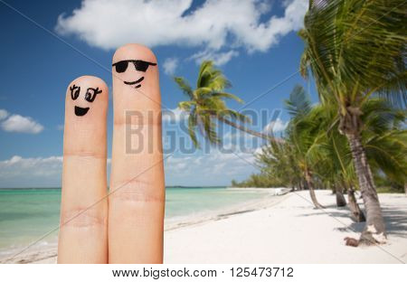 family, travel, summer holidays, tourism and body parts concept - close up of two fingers with smiley faces over exotic tropical beach with palm trees background