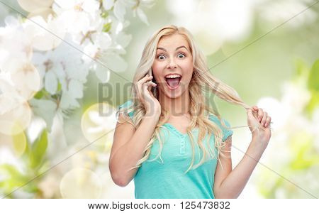 emotions, expressions, technology and people concept - smiling young woman or teenage girl calling on smartphone over natural spring cherry blossom background