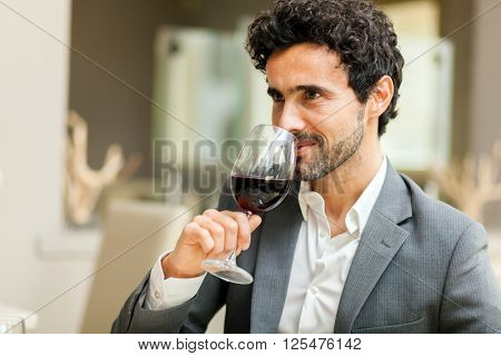 Man toasting wineglasses in a luxury restaurant