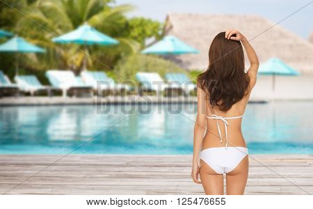 people, summer holidays, travel, tourism and vacation concept - woman in bikini swimsuit from back over exotic hotel resort beach with swimming pool and sunbeds background