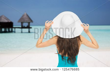 people, summer holidays, travel, tourism and vacation concept - woman in swimsuit and sun hat from back over maldives beach with bungalow background