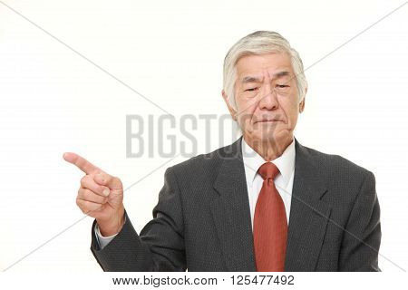 studio shot of senior Japanese businessman doubting
