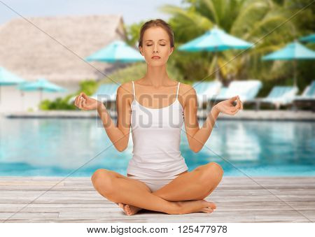 people, meditation, relax and wellness concept - young woman in cotton underwear practicing yoga lotus pose over exotic hotel resort beach with swimming pool and sunbeds background