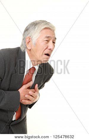 studio shot of senior Japanese businessman heart attack