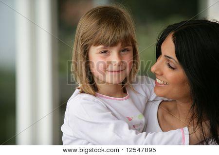 Retrato de uma menina sorridente nos braços de uma jovem mulher