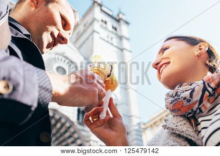A couple in love eat ice-cream during their Italian voyage