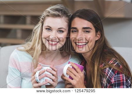 Two beautiful women sitting side by side on sofa with a mug of coffee at home