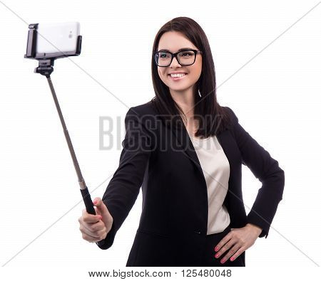 Young Business Woman Taking Photo With Smart Phone On Selfie Stick Isolated On White