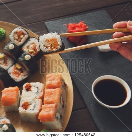 Japanese food restaurant, sushi maki roll plate, platter set. Hand take roll. Set with chopsticks, ginger, soy, wasabi. Sushi at rustic wood background and black stone. POV at black. Instagram style.