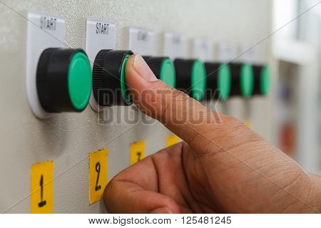Thumb touch on green start switch on control panel