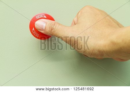 Thumb touch on red emergency stop switch on control panel