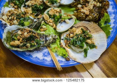 Fresh oysters in a plate with spice and lemon on a wooden desk
