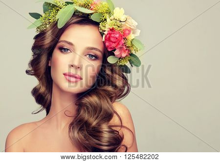 Beautiful woman  model brunette  with long curly hair floral wreath on the head . Spring girl . Summer fresh image