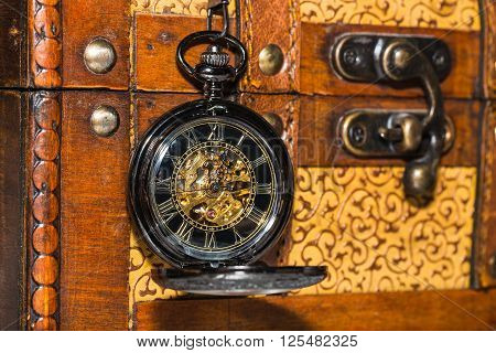 vintage pocket watch against the background of an old trunk