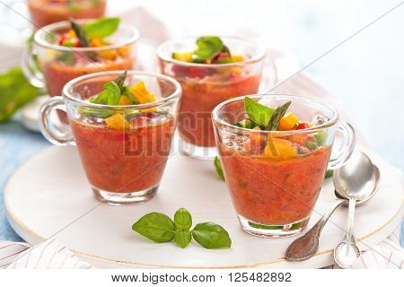 Cold tomato soup (gazpacho) in small cups on wooden cutting-board.