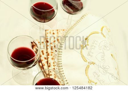 the symbols of the feast of Passover; three pieces of matzah; poured a glass of red wine; white cloth with embroidery and font on the Hebrew Pesach; on a white background