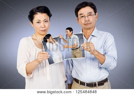 Asian couple holding a photo against grey vignette