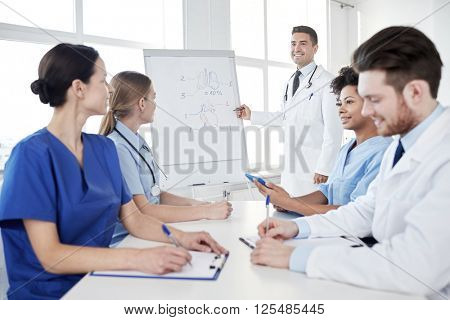 medical education, health care, medical education, people and medicine concept - group of happy doctors or interns with mentor meeting and drawing on flip board on presentation at hospital