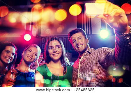 party, holidays, technology, nightlife and people concept - smiling friends with glasses of champagne and smartphone taking selfie in night club with holidays lights