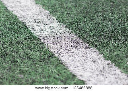 : Close up of white line on green grass football field.