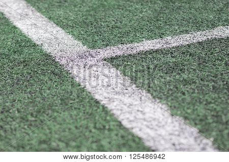 Close up of white lines on green grass football field.