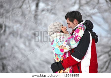 Young couple hugging in front of snowy trees