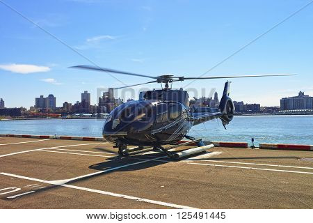 New York, USA - April 25, 2015: Black Helicopter on the helipad in Lower Manhattan in New York USA on East River. Pier 6.
