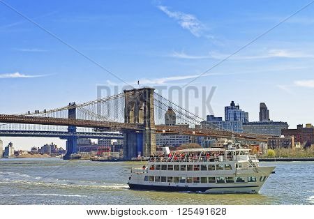 NEW YORK USA - APRIL 25 2015: Ferry near Brooklyn bridge and Manhattan bridge over East River. Tourists on board. Bridges connect Lower Manhattan with Brooklyn of New York USA. View of Brooklyn side.
