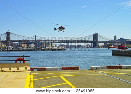 Helicopters near Brooklyn bridge and Manhattan bridge over East River. Bridges connect Lower Manhattan with Brooklyn of New York USA. Manhattan and Brooklyn Heights are on the background