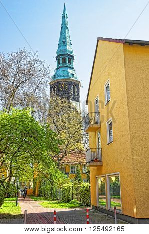 Street view on Church of Holy Cross in Hanover in Germany. Hannover or Hannover is a city in Lower Saxony of Germany. People nearby