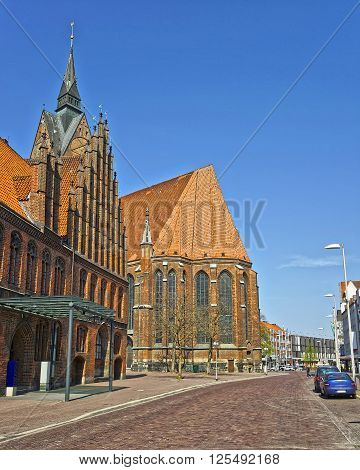 Hanover, Germany - May 1, 2013: Street view on Church on Market place and Old Town Hall on the Market Square in Hanover in Germany. The church is called Marktkirche. Hannover or Hannover is a city in Lower Saxony of Germany. Tourists nearby