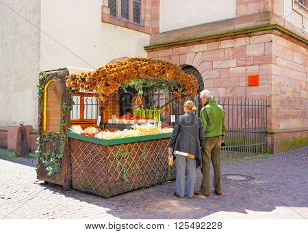 Tourists near Counter with fresh asparagus and strawberry in Heidelberg in Germany. Heidelberg is a city in Baden-wurttemberg in Germany.