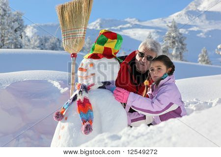 Little girl making a snowman with a senior man