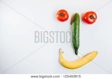 Happy face made with fresh fruits. Tomato cucumber banana. fruit face.joke.