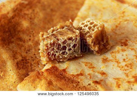 Hot golden homemade pancakes with fresh honeycombs