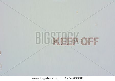Keep Off hand painted sign against a plain white metal background
