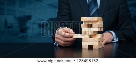Metaphor of risk in business. Risk management concept. Businessman remove one piece from tower wide banner composition with office in background. Nothing ventured nothing gained.