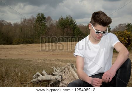 Teenage boy sitting on a log in a park