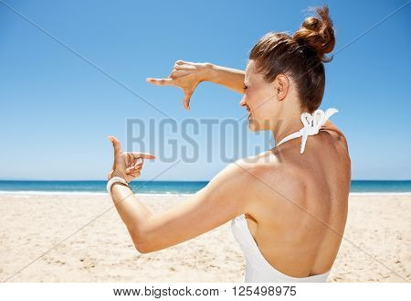Happy Woman In White Swimsuit At Sandy Beach Framing With Hands