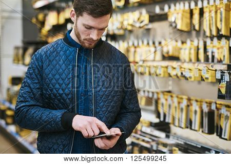 Young Man Checking A Text Message In A Store