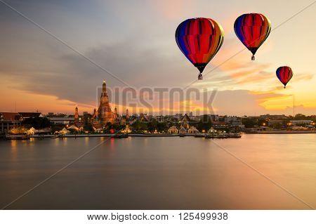 Colorful hot-air balloons flying over Wat Arun temple and Chao Phraya River Bangkok Thailand