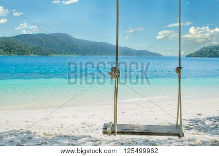 Summer Travel Vacation and Holiday concept - Swing hang from coconut palm tree over beach sea in Phuket Thailand.