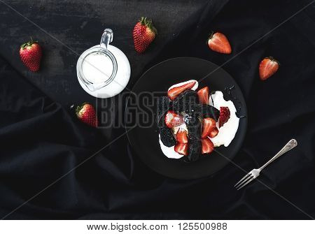 Black biscotti and strawberry dessert with sweet cream over black backdrop, top view