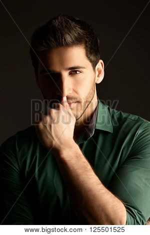 Handsome casual young man looking at camera and slightly smiling. Men's beauty. Studio shot over black background.